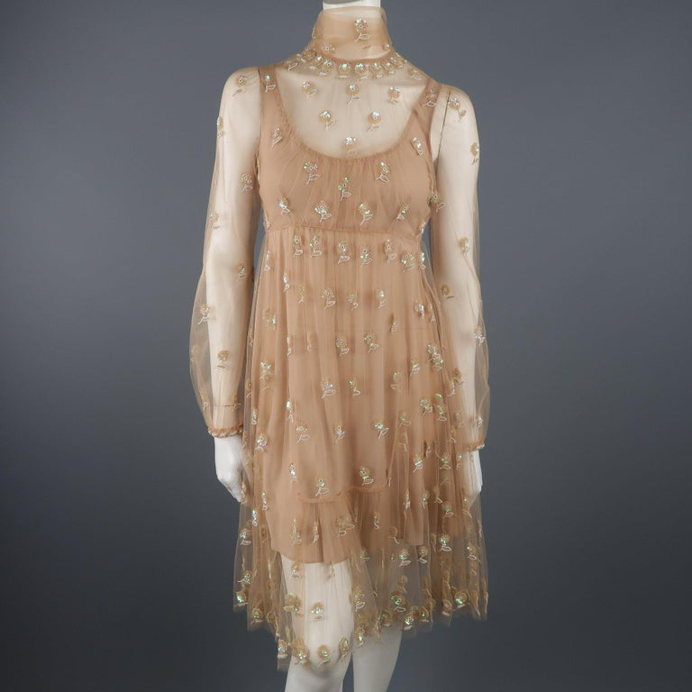 Valentino cocktail dress comes in tan tulle with all over beaded floral pattern, tied scarf neckline, long sleeves, full skirt, and silk lining. Made in Italy.   Excellent Pre-Owned Condition. Marked: (no size)   Measurements:   Shoulder: 12