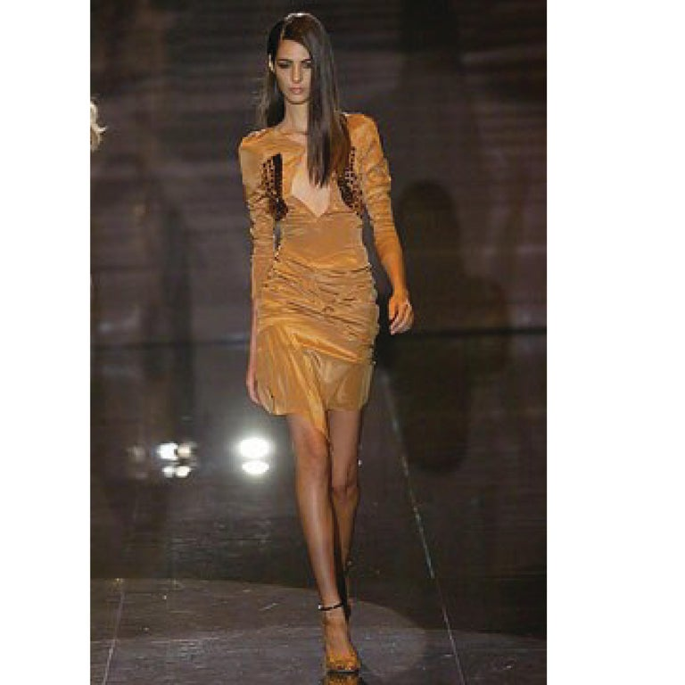 This fabulous archive GUCCI Spring 2005 cocktail dress comes in tan stretch silk taffeta with an open back, gathered and draped layered skirt, chest cutout, sheer bust panels with copper jewels, and long sleeves with metal accents. Made in Italy.