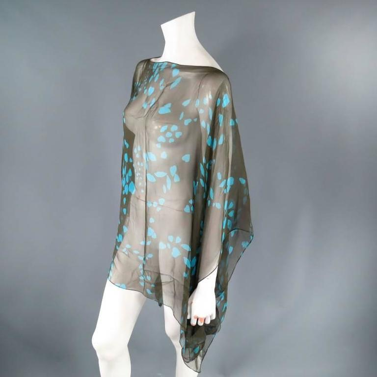 Fabulous scarf poncho by Yves Saint Laurent. This classic style comes in ultra sheer, light weight, olive green silk chiffon with aqua blue lip heart print and can be worn as a draped poncho top or as a neck scarf.   Excellent Pre-Owned Condition.