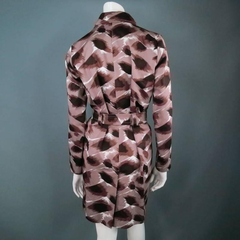 Chic taupe cotton trench coat by GUCCI. In a fabulous all over animal print resembling cheetah or leopard, featuring concealed buttons, gold hardware, and waist belt. A functional garment that is effortlessly glamorous. Made in Italy.   Excellent