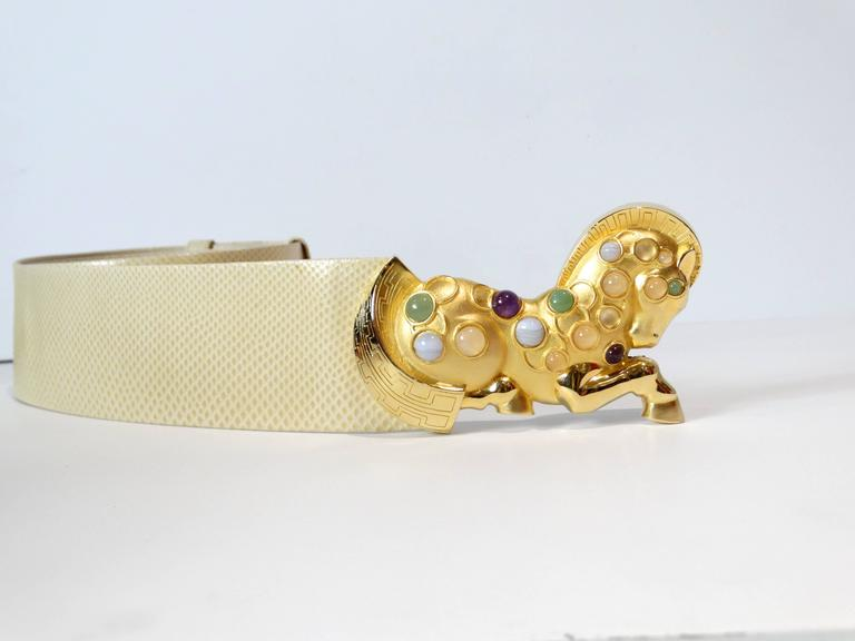 1980's Judith Leiber Golden Trojan Horse Buckle is embellished with lovely cabochon stones of Amethyst, Jade, White Marble Horse features polished and matte gold-tone metal. The horse's mane and tail are etched in an interpretation of a traditional