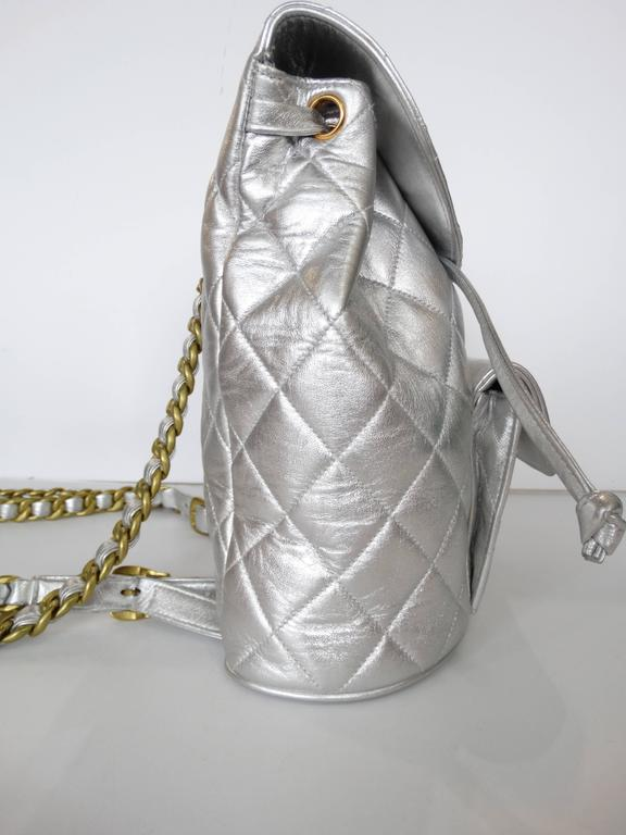 A rare 1990's Silver Chanel lambskin quilted metallic leather backpack with gold-tone hardware, adjustable straps, exterior flap pocket, drawstring closure and front flap interlocking CC turn lock closure. Serial number reads 2959239 . Still has the