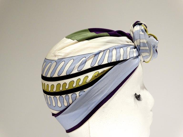 1990's Emilio Pucci rectangular silk scarf in a bold geometric print. Colors are white, black, sky blue, greens and deep purple. Hand rolled and hand stitched edges. Measures 48 x 8.6 inches great for wrapping (shown in images) signed Emilio through