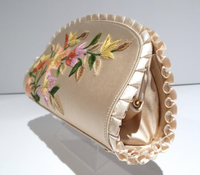 Exquisite Bohemian Judith Leiber original design clutch new with tags. This beautiful clutch features a wonderful floral embroidered detail. The superb champagne color silk is accented with a perfect knife ruffle pleat along the edges. The purse