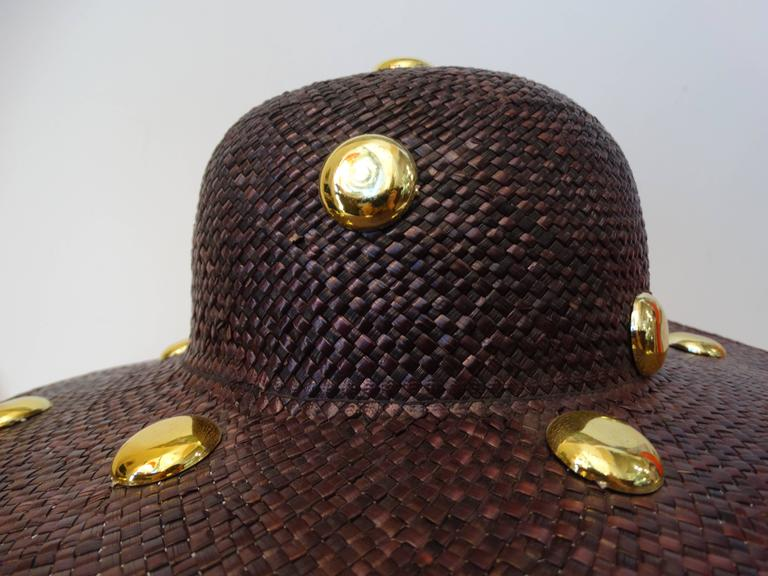 "Fabulous 1980's Saks Fifth Avenue wide brim straw hat with large gold studs. Dyed deep purple. The base of the crown is plain with large plastic gold studs. The opening of the hat measures 21 1/2"" around - this should fit a medium sized head. The"