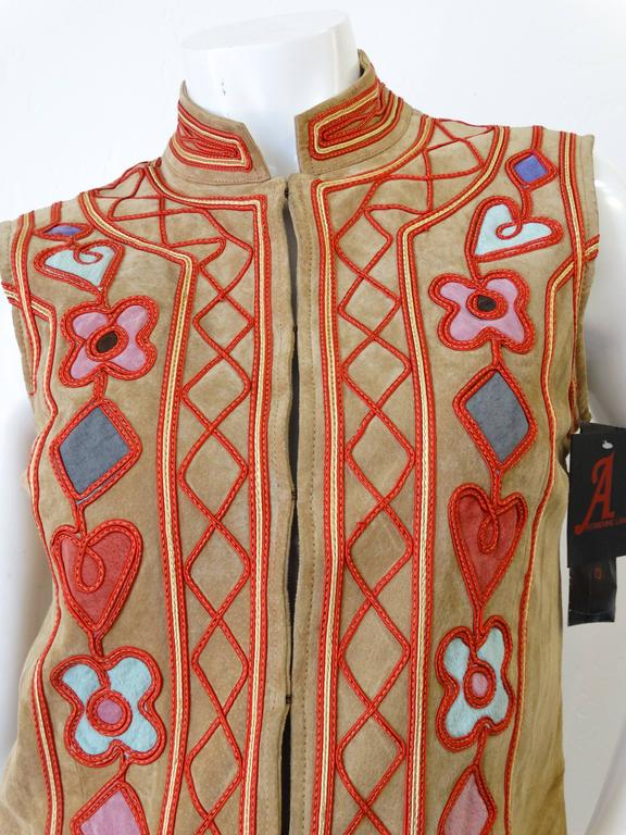 Adrienne Landau 90's does 70s bohemian suede vest! Hook and eye closures up the front. Hearts and floral motifs in multicolored suede accented with red embroidery. Original tags intact.