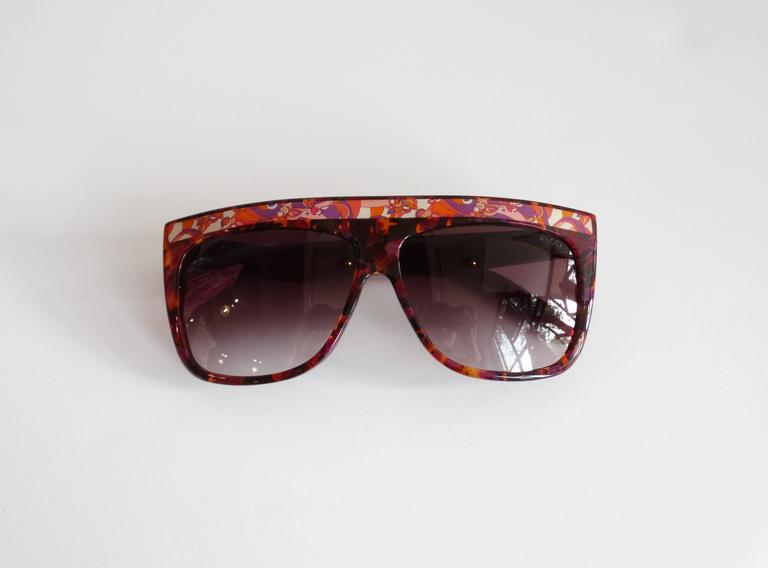 Fabulous 1990s Emilio Pucci Sunglasses! Multicolored tortoise shell confetti with Pucci's signature psychedelic prints along the brow and arms. Comes with original carrying case and bag. Made in Italy 5 1/2 inches across the brow