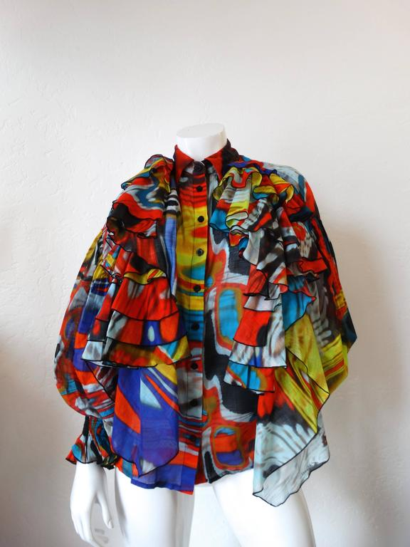 Avant Garde Just Cavalli Camicia Ruffle Top. Buttons up the front. Dramatic flared sleeves with cinched, elasticized cuffs. With ruffle detail at both shoulders. Psychedelic multicolored marble print. New with tags, never been worn. Marked a size