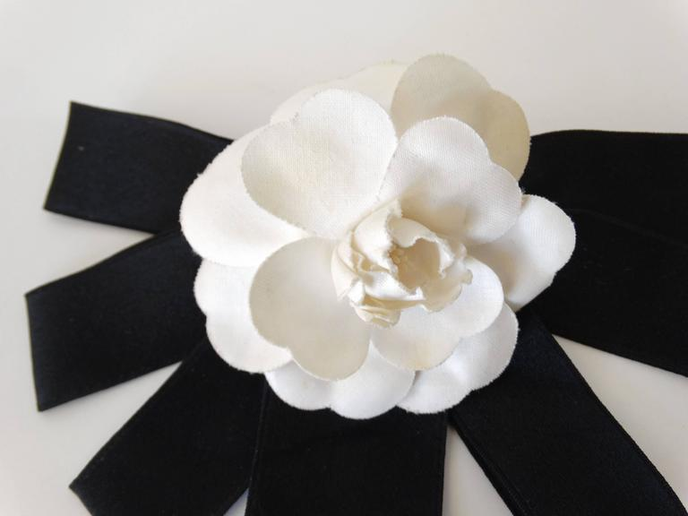 1980's rare large Chanel Camellia flower hair barrette with 7 pieces of ribed ribbon which form a half circle. 9 inches across Chanel signature plate attached on the back. Dates to the 1980s