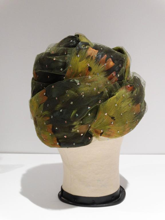 Glorious Colored 1960's Pheasant feathered turban with a touch of sparkle, enrobed in a wispy green netting atop a beautifully rounded form... all of this and the Iconic Milliner's Label to add......Christian Dior!! This Turban is in Fabulous shape,