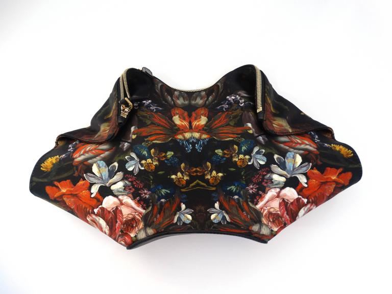 """Incredible silk satin Botanical printed Alexander McQueen De Manta Clutch. Magnetized folds at either side. Unzips along the top. Fully lined interior with zip pocket Goldtone hardware. 15""""L x 8""""H x 2""""D. A true piece of art!"""