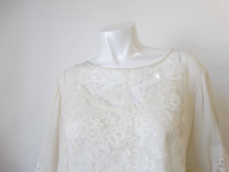 Cut From Flattering Stretch-Silk. In A Versatile Ivory Hue, This Wear-Anywhere-With-Anything Oscar De La Renta Blouse Stands Out For Its Lace Appliqued Sleeves And Elegant Bell Sleeves That Snap At The Cuffs. Comes with a gorgeous silk camisole.