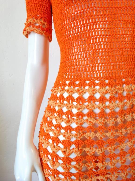 Incredible 1970's orange knit gown! Vibrant two-tone orange tighter knit on the top with a more open crochet fabric from the waist down. metal zipper that zips up the back. Crochet ruffle neckline and sleeve! Even better in person.