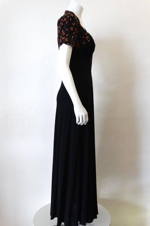 The most amazing 1940s glass beaded gown! Classic 40s silhouette with short sleeves and sweetheart neckline. Slightly sheer black Rayon with orange and pink botanical beading on the shoulders. Flattering ruched bustline. Zips up the side. Fits a
