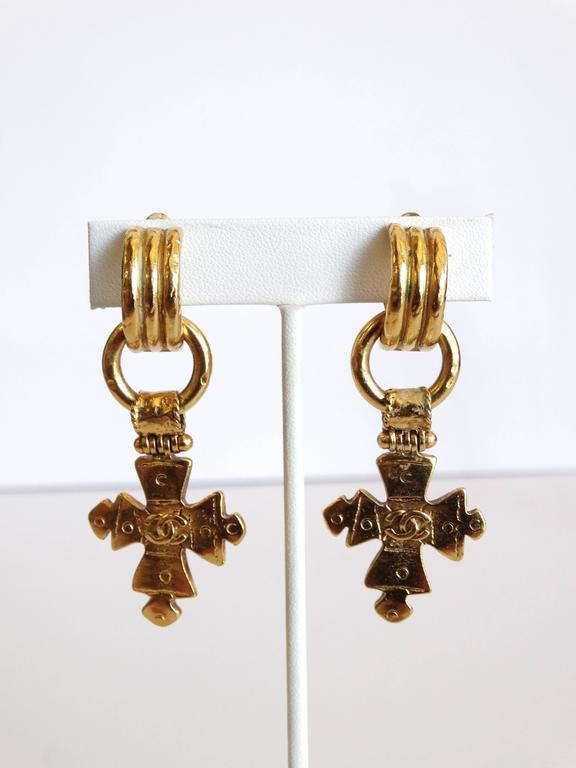 Incredible pair of Chanel cross earrings! From Spring 1994- these earrings come to you in a brilliant gold metal with double cc cross charms that are detachable- can be worn with or without. Made in France engraved on the back. They look truly