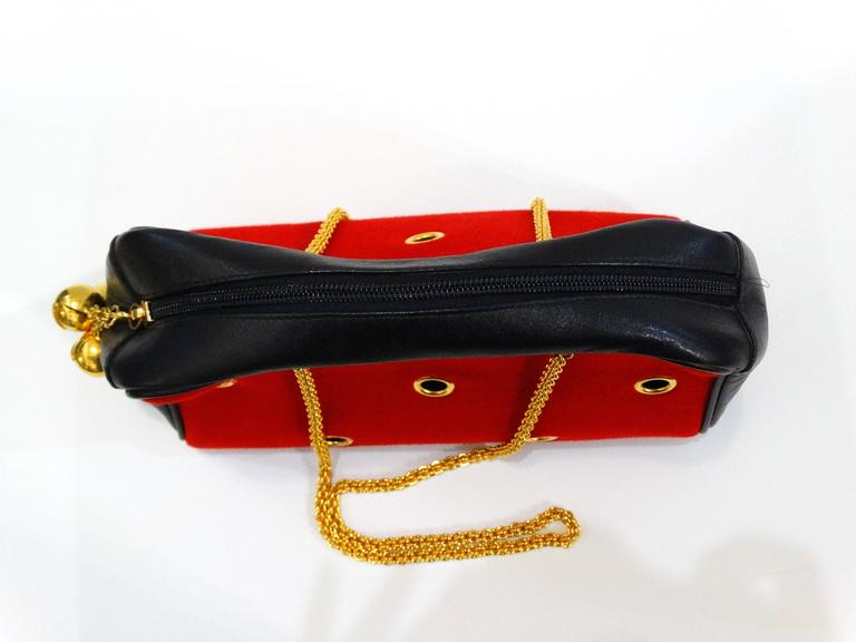 Incredible Moschino Redwall Grommet bag! Red cloth exterior with gold grommet details. Bell charm zipper pull with Moschino signatures. Long gold twisted chain straps. Great size 14inches x 8 inches x 4 inches