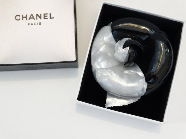 This stunning brooch is crafted of individual plates of highly polished petals to create a large black and white camellia flower with a brass pin on the back. This is a marvelous brooch to add a touch of chic to your wardrobe, from Chanel! Chanel's