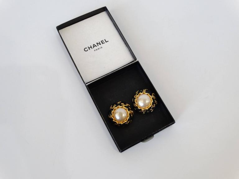 Amazing 1980s Chanel Oversized pearl earrings! Large faux pearls accented by 2 rows of gold chain detail with actual black leather woven throughout. Clip on style, signed at the back. Comes with original box.  Made in France