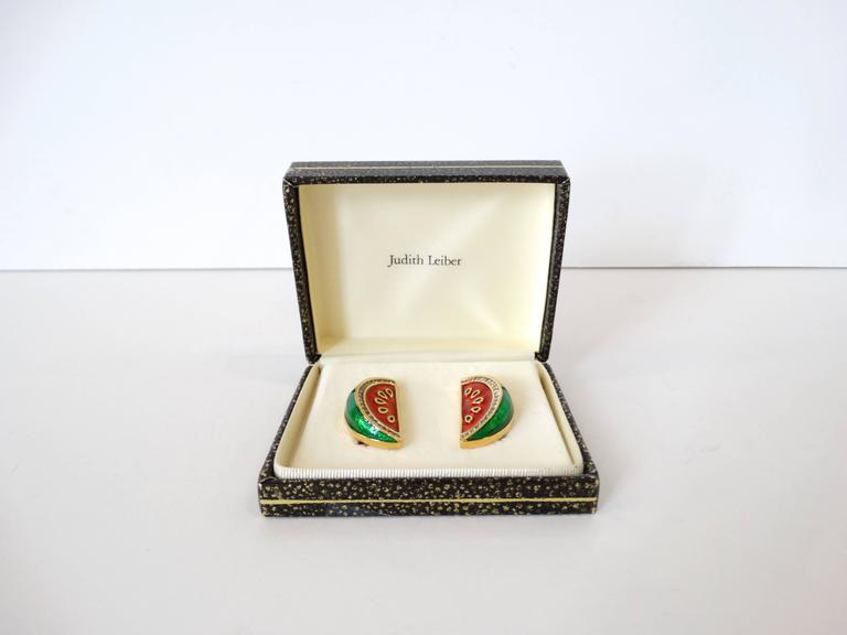 Adorable pair of Judith Leiber watermelon earrings! Gold metal with red and green enamel- accented with crystals along the rind. Clip on backs. Signed at the back. Comes with original box.