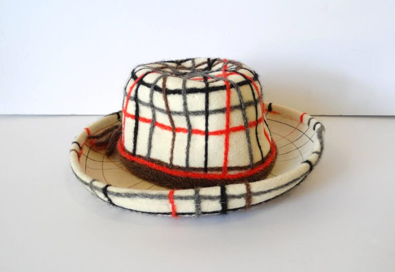 The classiest little plaid Yves Saint Laurent hat! very unique!! It is a cream colored wool accented with strands of grey, orange, black and brown wool yarn. It has a cute little pony tail of yarn at the back of the hat. Great piece for display, to