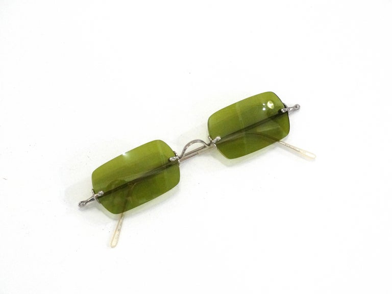 Colored sunglasses are SO en vogue- rock this pair of Oliver Peoples' sunglasses in a rare olive green color! Silver wire hardware. Comes with original leather case.   Lens Height: About 1 inches Lens Width: About 2 inches