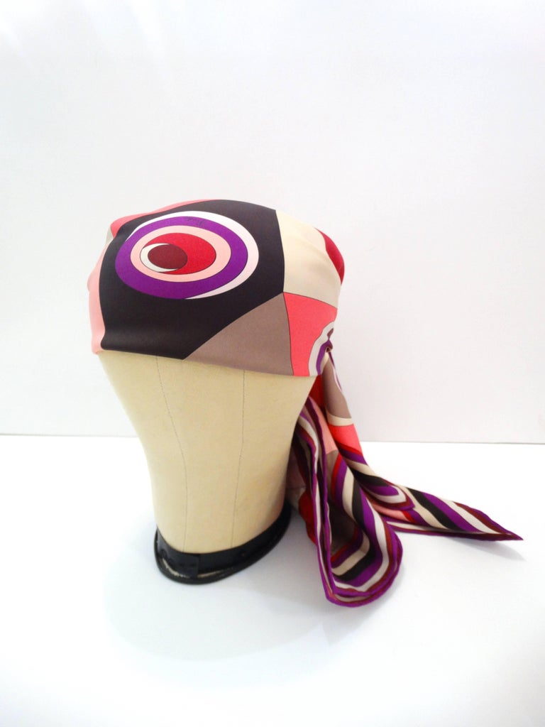 Gorgeous 1990s silk scarf from designer Emilio Pucci! Bright pops of pink, purple and red on a bold geometric print! 100% silk and 100% versatile- can be worn as a headscarf, around the neck, tied on a bag, you name it! The possibilities are