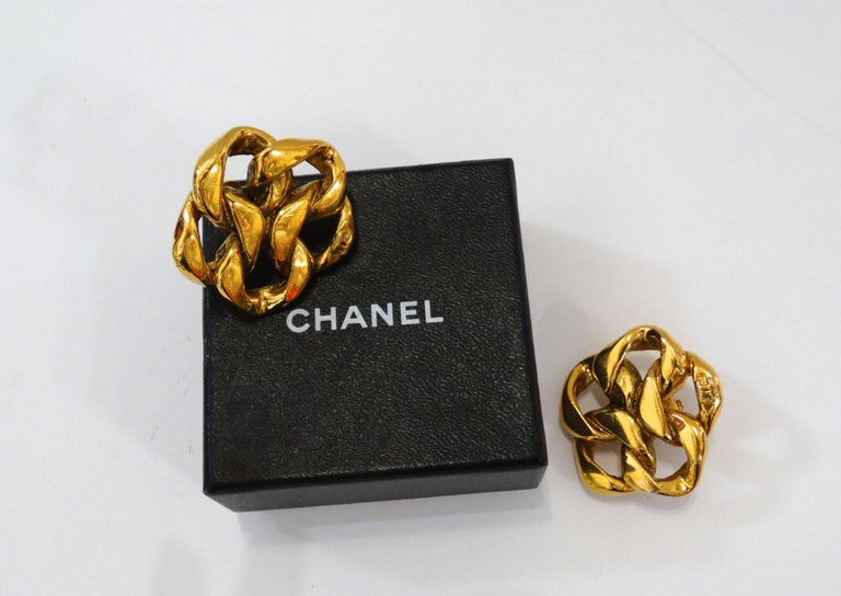 Make a statement in our 1980s Chanel Chain earrings! Thick gold chain link arranged in a flower like silhouette. Small CC signature at the bottom of each earring. Clip on backs. Signature beneath clip fixtures. Signed Made in France Chanel 2 3