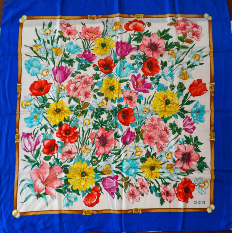 """Beautiful 1970s Flora  Gucci scarf in brilliant multicolored floral print! Royal blue edges with insignias at the corners. Made of 100% silk.  35"""" by 35"""" Handrolled edges made in Italy"""