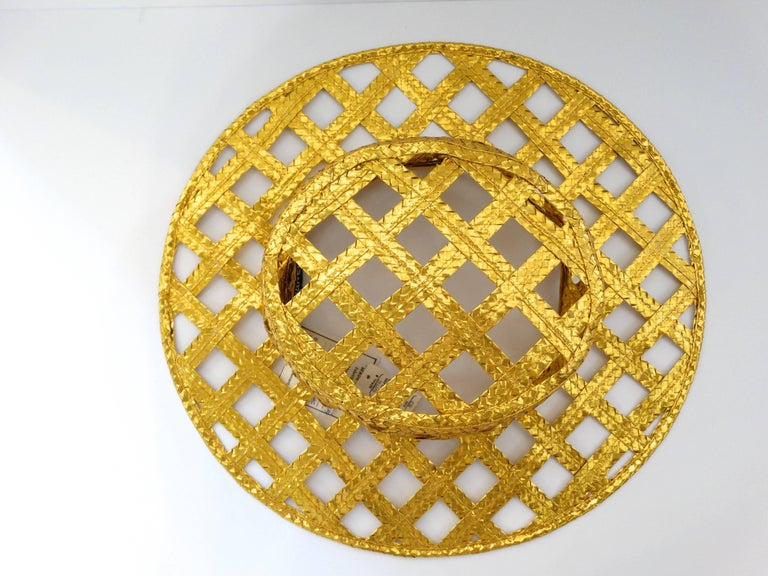 Fabulous Chanel gold lattice hat with tags attached. This hat is gold woven and ultra shiny with a foil like effect. From Spring of 1990 this hat was originally purchased from the West Palm Beach Chanel Boutique over 27 years ago. Such a statement