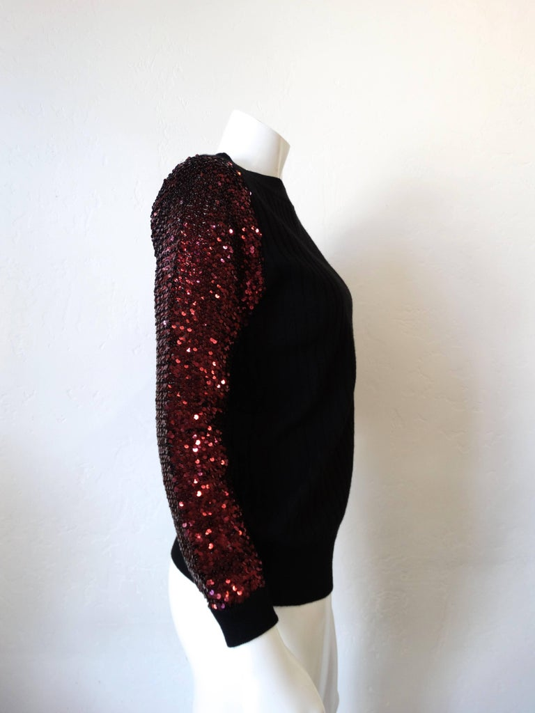 "Get festive in our 1970s Saint Laurent Rive Gauche sweater! Black knit ribbed fabric with magenta sequin sleeves! Fabric has some stretch to it which allows for a number of sizes to enjoy!    Marked a size 38 Bust: 38"" Length: 25"" Sleeve: 28"""