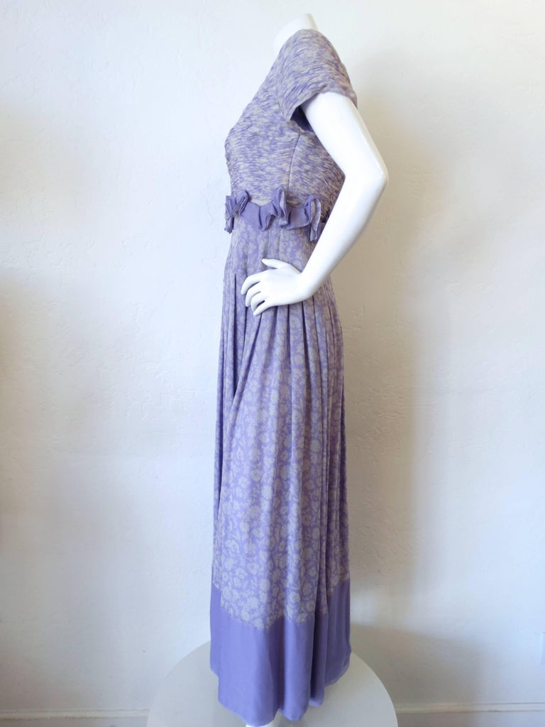 Amazing 1970s Valentino Boutique lilac gown! Lavender and white floral print accented with matching solid fabric. Short sleeve fit with a boat neckline. Ruffle detail at the waist above the gorgeous pin tucked seams that cascade down the length of