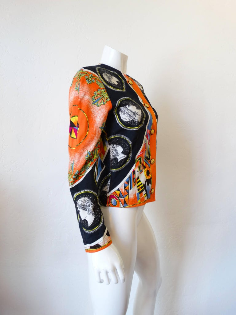 The most fabulous jacket from prolific designer Gianni Versace. This piece has an older label that indicates its from an earlier Versace line, before the atelier lauched. This piece features detailed construction with gold metal medallion buttons up
