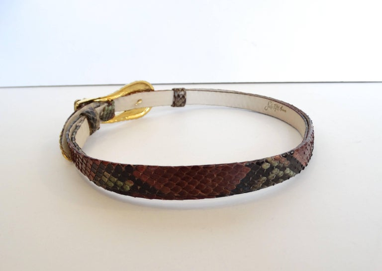 Amazing 1980s buckle belt from the iconic designer Judith Leiber for Saks Fifth Avenue! Gold metal belt buckle with silver crown accent. Hooks in the front beneath the buckle. Thin multicolored snakeskin belt adjusts to whatever size you want by