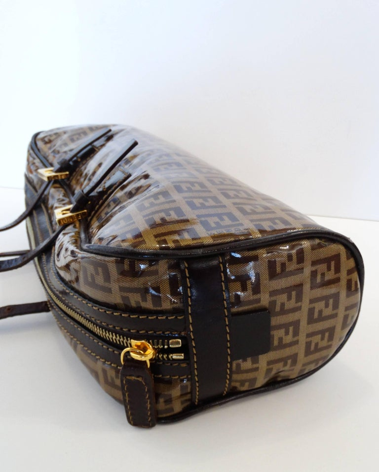The most adorable little top handle Fendi bag in the brown Zucchino print! Monogram logo printed jacquard fabric with an overlay of vinyl. Dark brown leather straps with gold metal buckles and zipper. Fully lined fabric interior with zipper pocket.