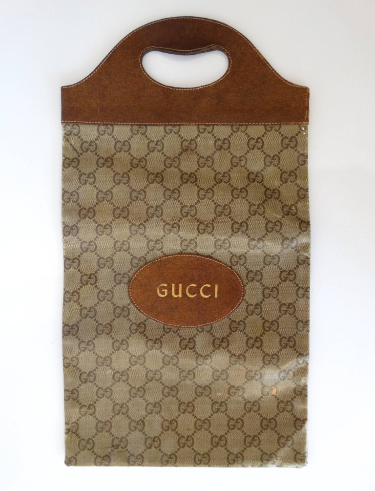 You're going to want to get your hands on this while it lasts: super rare 1970s Gucci monogram hand bag! Long, tote like style can be carried by the top handle or folded over like a clutch. Gucci monogram fabricbtopped with clear glossy vinyl