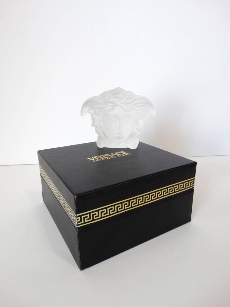 Add some vintage to your desk decor with our Versace paperweight! Classic Versace Medusa head silhouette made of a heavy semi translucent frosted glass! Made in collaboration with Rosenthal! Signed at the bottom with Rosenthal x Versace. Comes with