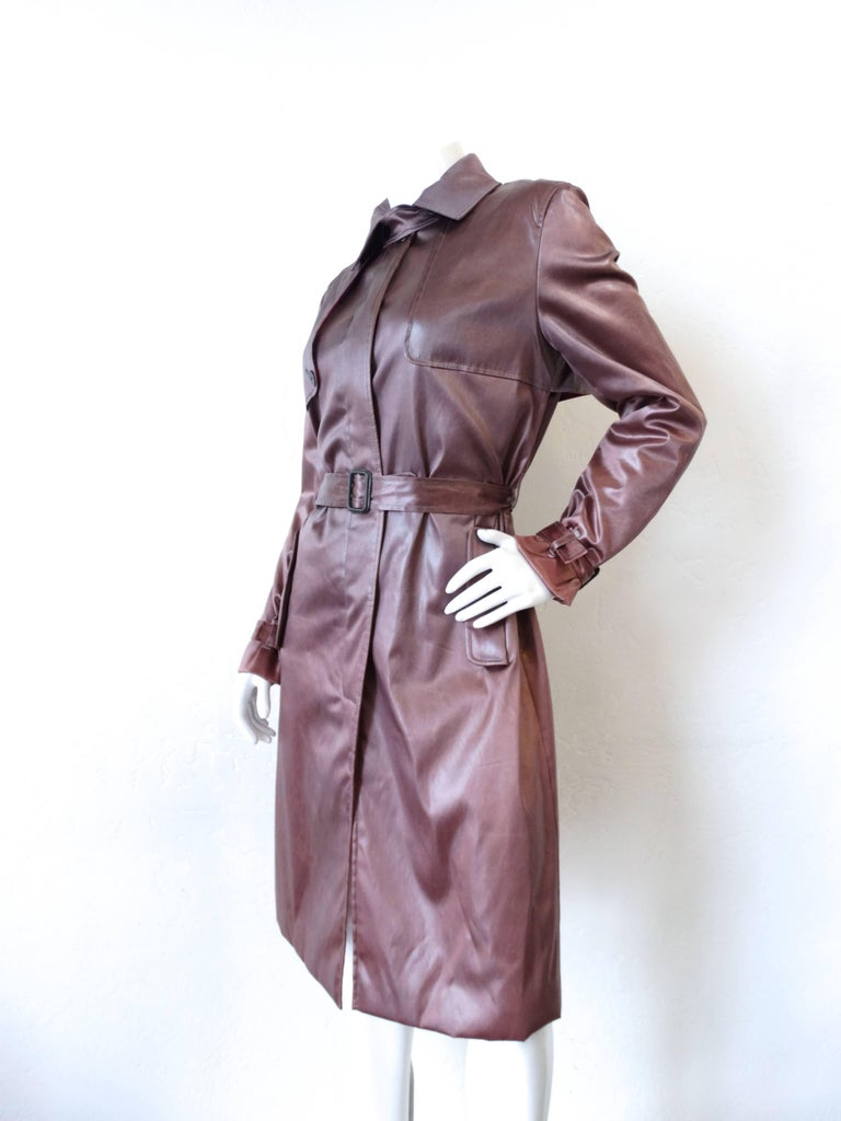 Nothing like a little bit of Pucci to liven up your outerwear collection! Super silky soft satin in this amazing dark dusty lilac color. Classic trench coat construction with a slightly cropped fit. Buttons up the front with hidden button