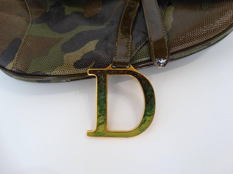 Christian Dior saddle bags are back in a big way! Here's your chance to nab yourself a saddle bag in the rare camouflage color-way! Made of a glossy mesh embossed camo printed leather. Hidden velcro closure beneath the top flap. Gold CD metal strap