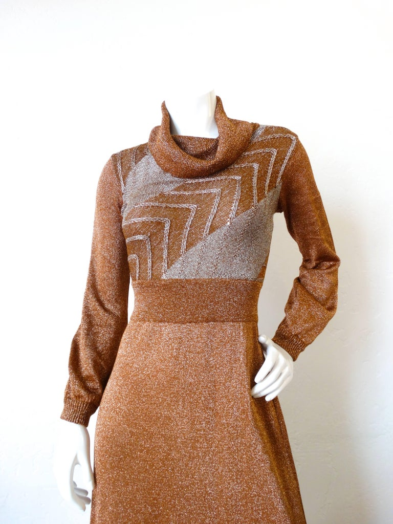 Rock some 1970s goodness this holiday season with our Wenjilli gown! Made of a super metallic lurex knit fabric in shades of silver and bronze. Chevron stripe pattern on the bodice with a banded waist. Gathered turtleneck-like neckline. Sleeves