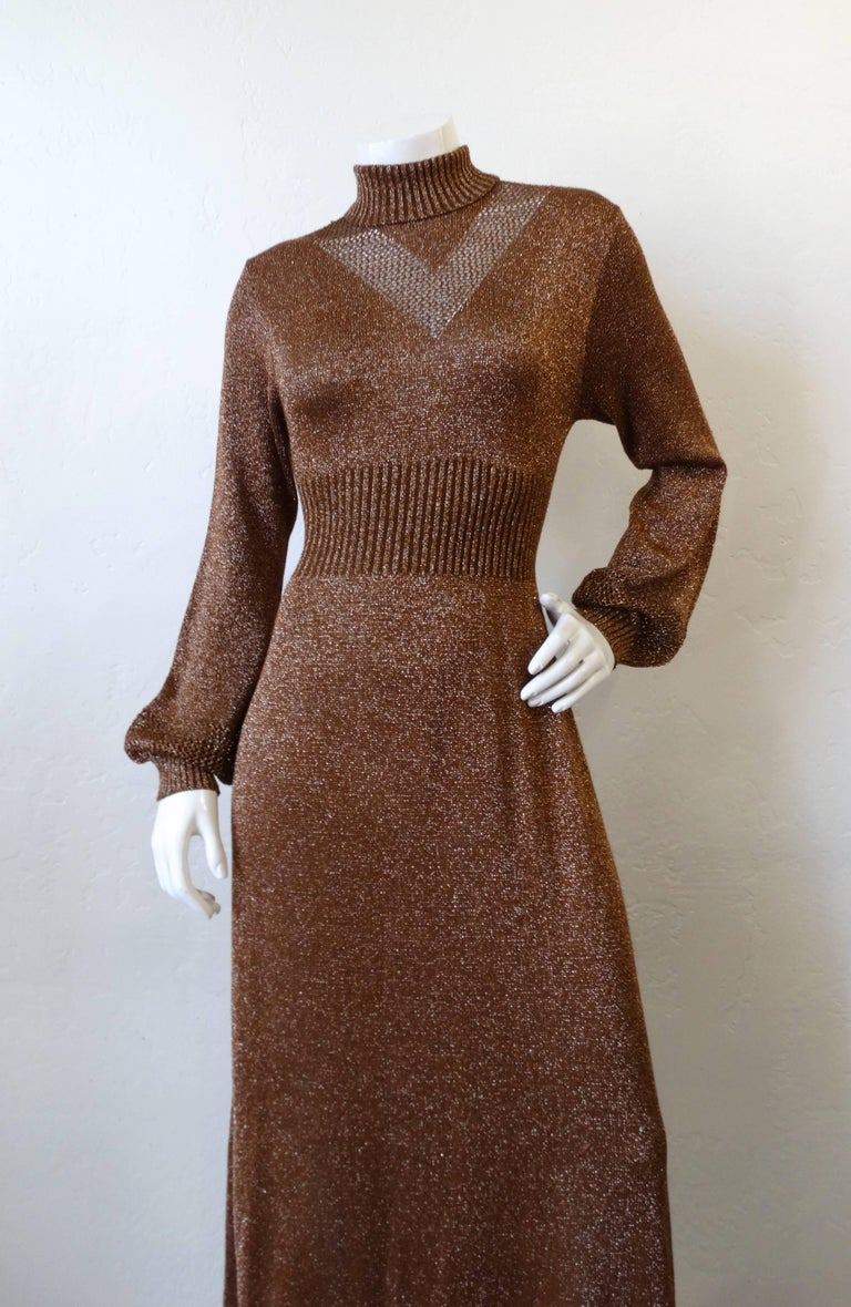 We love Lurex- and you will too with our 1970s Wengilli Lurex knit dress! Made of a super shiny bronze glitter lurex knit fabric with a chevron stripe panel on the chest in a more open weave. Ribbed turtleneck, waistline and cuffs. Maxi length and
