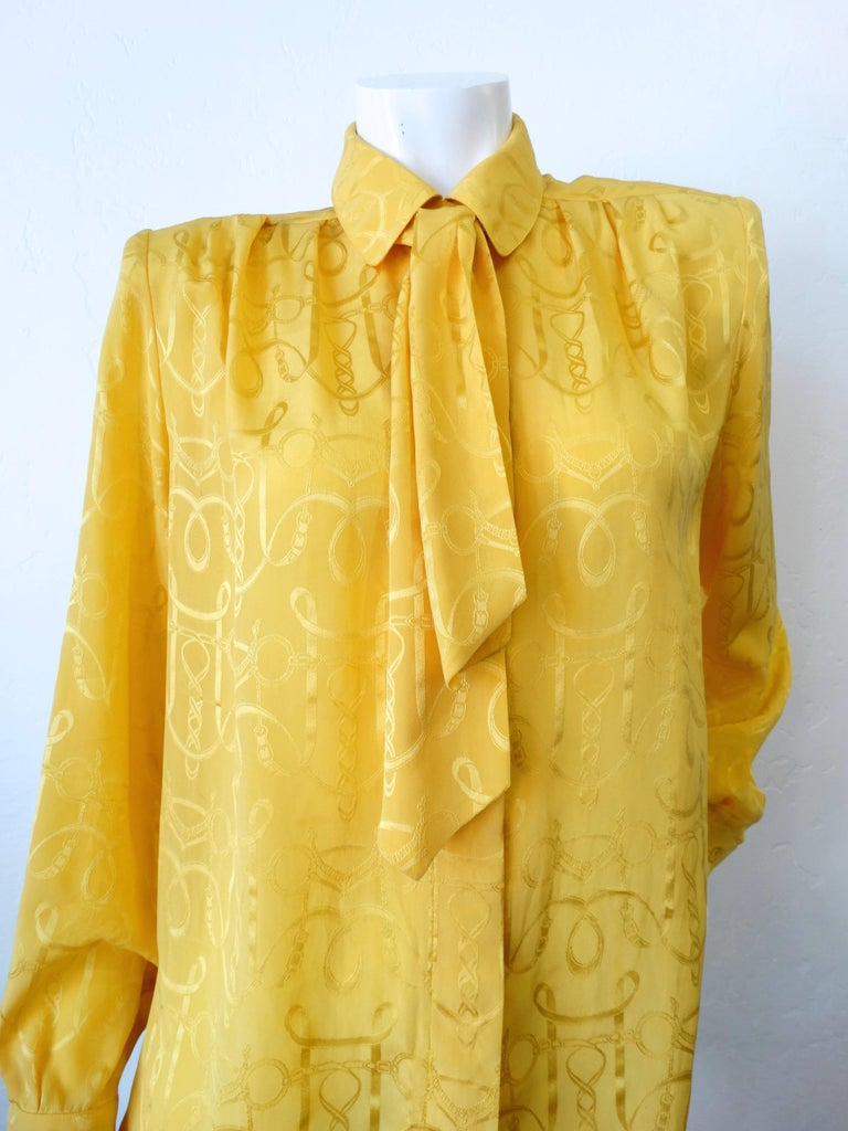 We're loving this strong shouldered blouse from iconic designer Hermes! Bright gold silk fabric with subtle rope print. Ascot is detachable, can be worn tied around the neck in the knot of your choosing. Buttons up the front as well as at the cuffs.