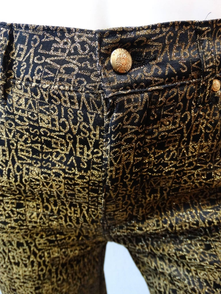 Amazing 1990s Versace monogram pants! Black and gold glitter Versace repeating print all over. Four pocket construction, clear versace patch on the back right pocket. High rise fit with a tapered leg. Zips up the front and buttons at the waist.