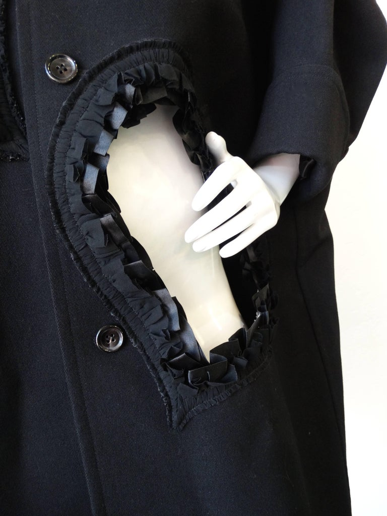 Fall in love with this incredible Comme Des Garcons heart cut out coat! Made of a soft black wool blend with cut out hearts throughout, all trimmed with black ribbon cut around the edges. Buttons up the front with big black glossy buttons. Fold over