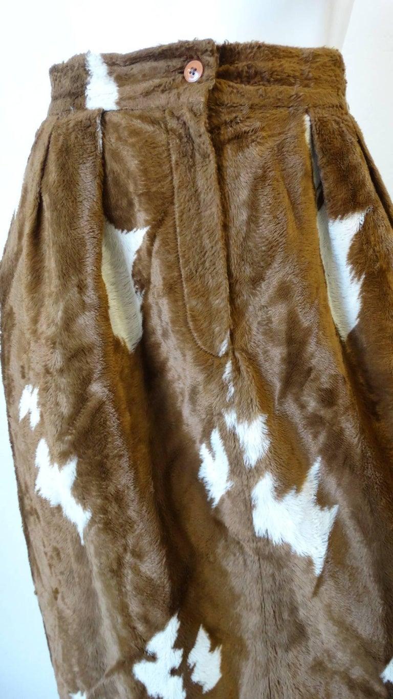 Cowgirl up with our amazing 1990s faux cowhide fuzzy pencil skirt! Made of a soft fuzzy faux fur fabric, printed with brown and white cow spots. Pencil skirt silhouette with high waisted fit and puckered waistline. Zips and buttons up the front.
