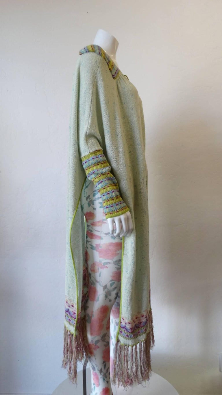 Rock the spirit of the 1970s with our amazing 1970s knitted duster jacket from London label, Bill Gibb! Spring/Summer 1976 collection Soft creamy knit contrasted with striped knitted sleeves, yoke and pockets. Long fringe yarn trim along the bottom.
