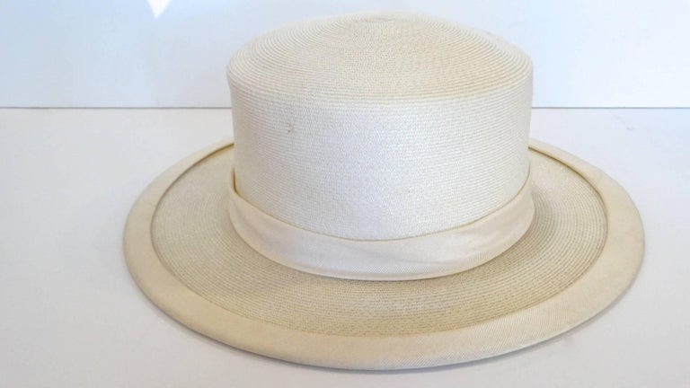 Panama meets the 70's! This exquisite panama style hat features a wide brim, with a gross grain sash, and adorned with two pom poms. The perfect summer hat! This hat measures 3.5