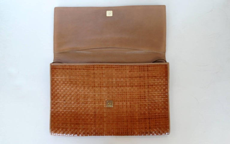 This authentic 1980's Fendi Clutch is the perfect seasonal bag. This woven leather clutch is trimmed in tan leather with gold Fendi accents. Interior of bag is tan leather and has a detachable shoulder strap. From Summer to Winter, this classic