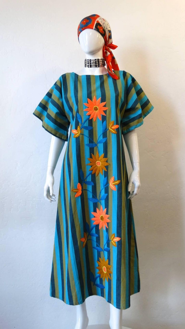 Your perfect summer cotton kaftan has arrived- with our adorable 1970s stripy embroidered maxi dress! Made of a breezy, quality cotton in a blue and green vertical stripe! Embroidered all over the front with orange flowers and blue leaves!  Angelic