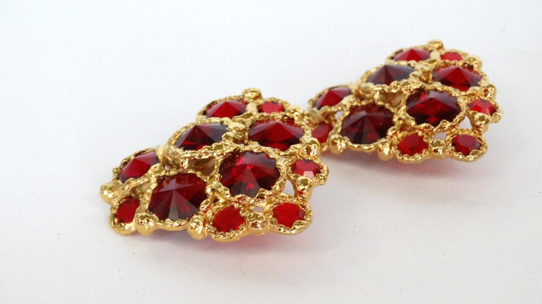 Spread the love with these Christian Lacroix heart shaped statement earrings! Circa 1980's, these clip-on earrings are crumpled textured gold plated with red gripoix gems throughout. Signed Christian LaCroix Made in France on the back of earrings.
