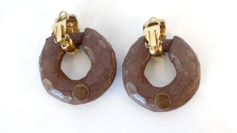 Make A Statement This Fall With These Kalinger Paris Earrings! Hanging off of a textured gold plated clip on closure these hoop earrings, resembling carved wood, are made from a brown resin and features amber colored rhinestones. Signed Kalinger.